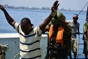 An Armed Forces for the Defense of Mozambique boarding team member searches a simulated illegal fisherman during an exercise. By Tech. Sgt. Chad Thompson (https://www.dvidshub.net/image/1053816) [Public domain], via Wikimedia Commons